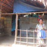 a lady infront of her house, Kaani tribe